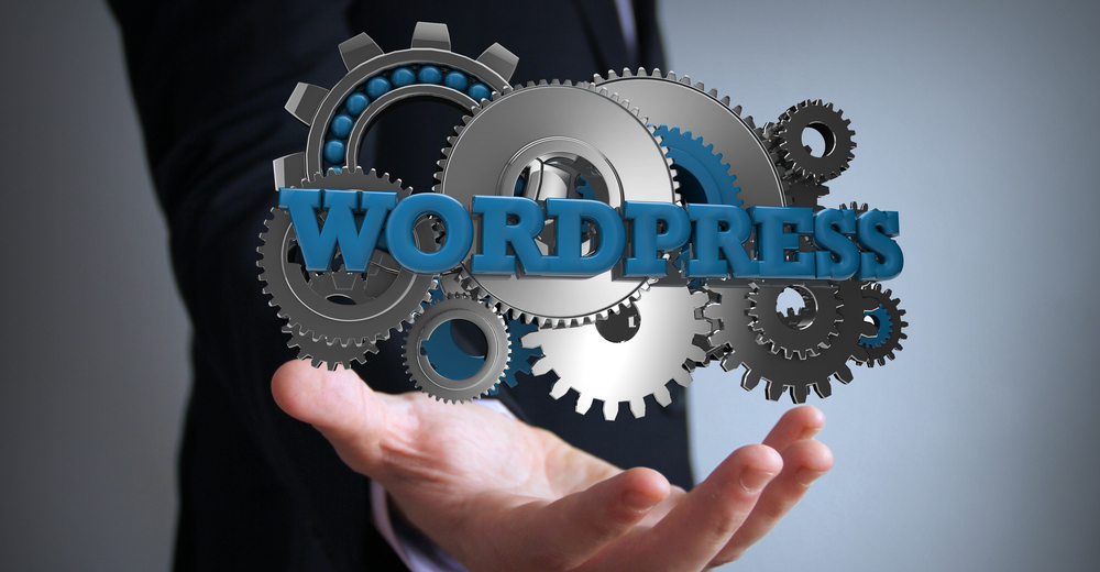 'WordPress' written in blue over grey cogs and hovering over the hand of a man wearing a suit.